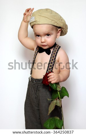 Little boy in cap, suspenders and bow-tie with one hand on a cap and holding a red rose in another one greeting somebody, isolated portrait on white background, romantic and love concept