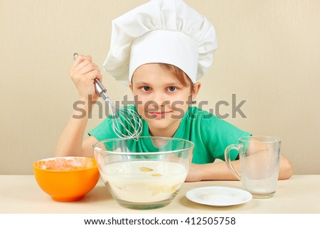 Little boy in chef hat prepares the dough for baking the cake - stock photo