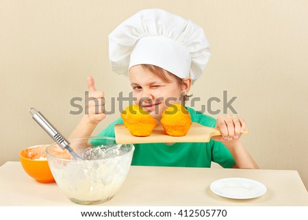 Little boy in chef hat with a cooked the appetizing muffin - stock photo