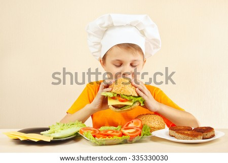 Little boy in chefs hat is tasting the cooked hamburger - stock photo