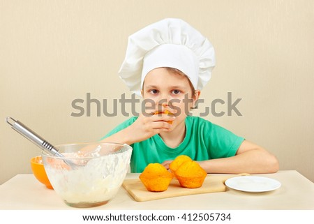 Little boy in chefs hat is tasting the cooked homemade cake - stock photo