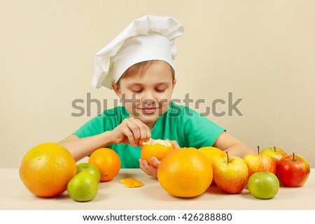 Little boy in chefs hat peeling fresh orange at the table with fruits - stock photo
