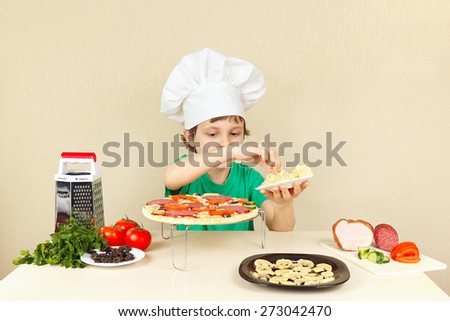 Little boy in chefs hat puts a grated cheese on the pizza crust - stock photo
