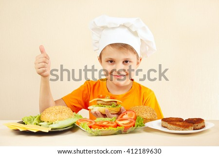 Little boy in chefs hat shows how to cook a hamburger - stock photo