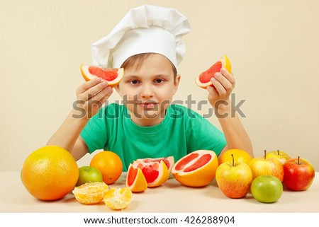 Little boy in chefs hat with two slices of grapefruit at the table with fruits - stock photo