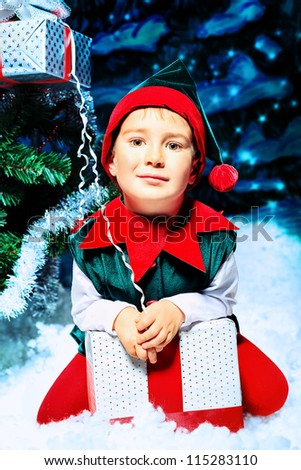 Little boy in Christmas elf costume posing over christmas background. - stock photo
