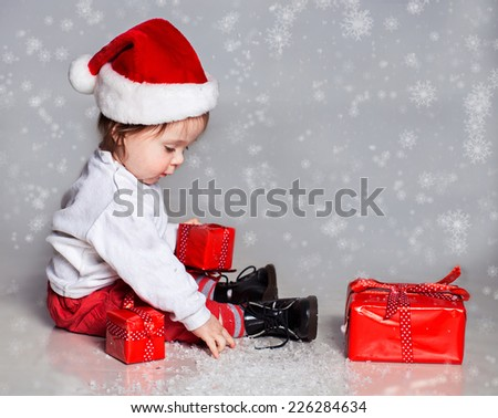 Little boy in christmas hat playing with presents - stock photo