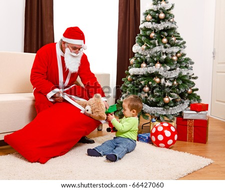 Little boy in Christmas, taking out toys from Santa Claus's bag