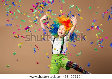 Little boy in clown wig jumping and having fun celebrating birthday. Portrait of a child throws up a multi-colored tinsel and confetti. Birthday boy. Positive emotions.  - stock photo