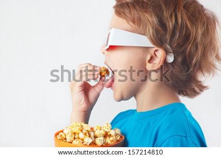 Little boy in 3D glasses eating popcorn  - stock photo
