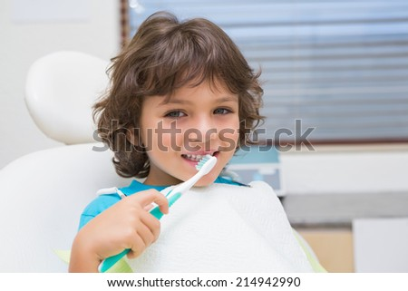 Little boy in dentists chair using toothrbrush at the dental clinic - stock photo