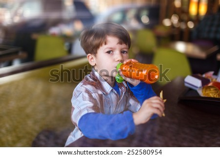 Little boy in fast food restaurant drink juice from bottle - stock photo