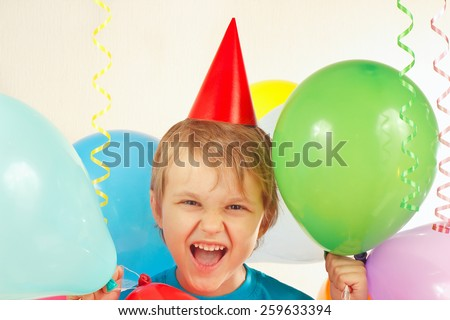 Little boy in festive hat with holiday balls and a streamer - stock photo