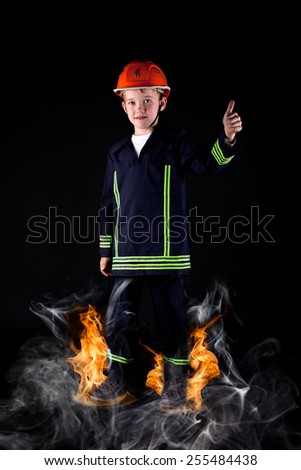 little boy in firefighter uniform with flames and smoke on the ground - stock photo