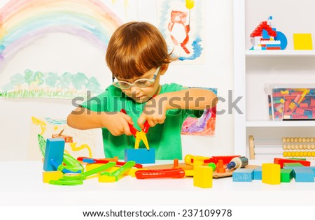 Little boy in glasses learning to use pliers - stock photo