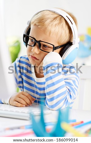 Little boy in glasses looking at computer screen - stock photo