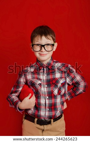 Little boy in glasses with a heart of toy in hands