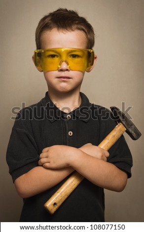 Little boy in goggles with a hammer - stock photo