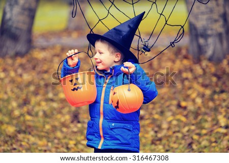 little boy in halloween costume in autumn park, kids trick or treating