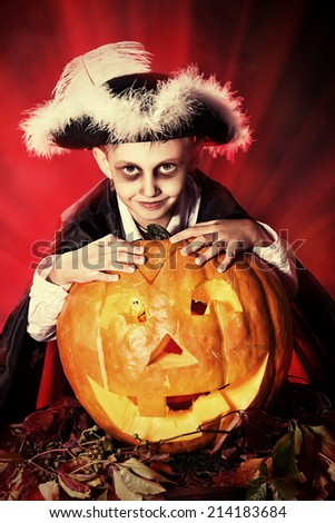 Little boy in halloween costume of pirate posing with pumpkins over dark background . - stock photo