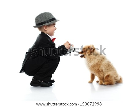 Little boy in hat and black suit with vintage camera  taking shot of little spitz - stock photo
