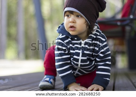 Little boy in hat concentrated - stock photo
