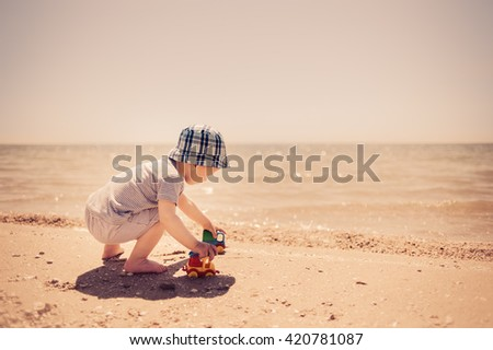 little boy in hat on the seashore