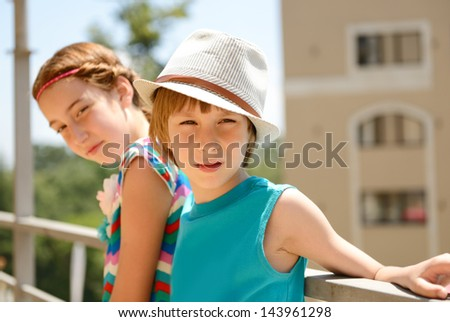 little boy in hat with attractive girl, summer outdoor portrait - stock photo