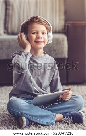 Little boy in headphones is listening to music using a digital tablet and smiling while playing at home