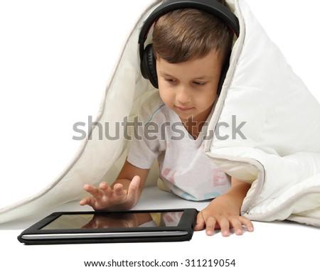 Little boy in headphones uses tablet lying under white blanket on white background - stock photo