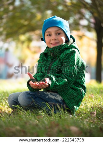 Little boy in jacket and hat sits on grass stretching his arms