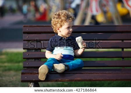 Little boy in jeans eats ice cream