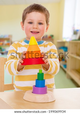 little boy in kindergarten collects colorful pyramid - stock photo