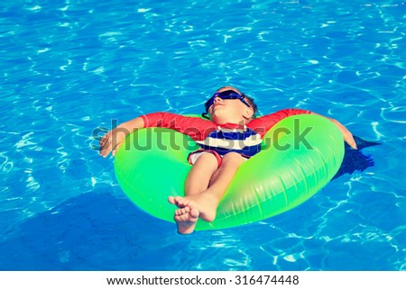 little boy in life ring having fun at the swimming pool - stock photo