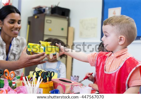 Little boy in nursery showing his teacher the cereal box car he has made. - stock photo