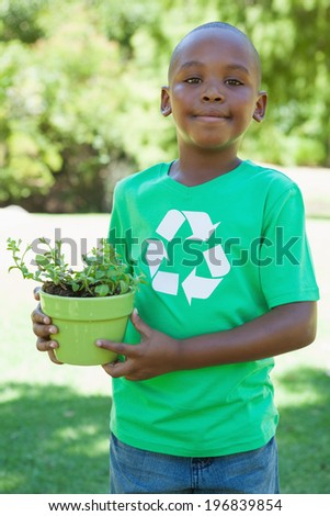 Little boy in recycling tshirt holding potted plant on a sunny day - stock photo