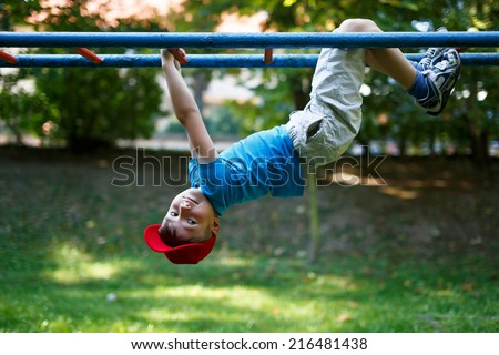 Little boy in red cap upside down at playground, outdoor activity, dangerous - stock photo