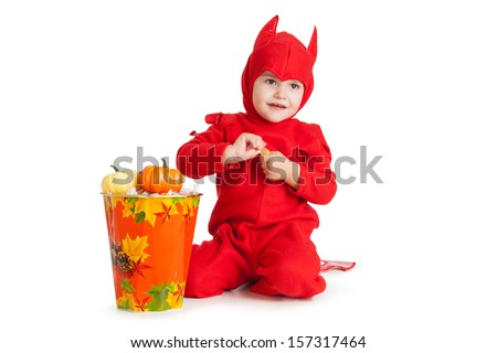 little boy in red devil costume sitting near big bucket with pumpkins over white background - stock photo