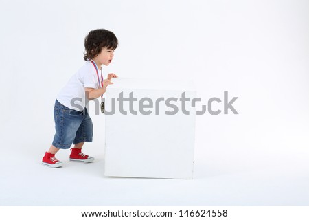 Little boy in red sneakers pushes large white cube on white background. - stock photo