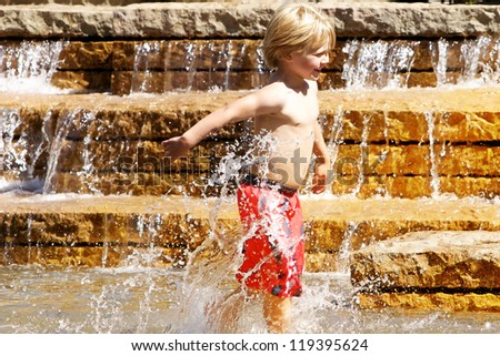 Little boy in red swimtrucks splashing in water fountain - stock photo