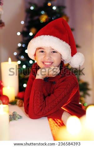 Little boy in Santa hat near fireplace in room