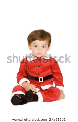 Little boy in Santa outfit on a white background.