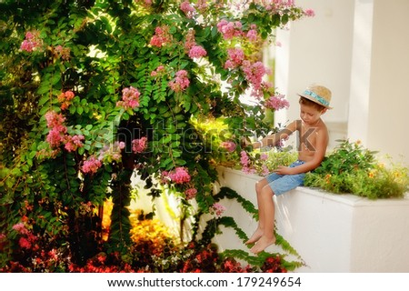 little boy in shorts and straw hat in a flower garden at home - stock photo
