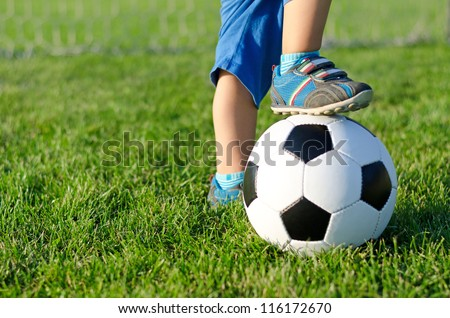Little boy in shorts and trainers with his foot resting on top of a soccer ball on green grass with copyspace