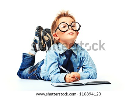 Little boy in spectacles and suit lying on a floor with a diary. Isolated over white background.