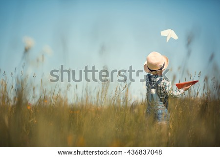 Little boy in straw hat is launching paper planes. One plane is white and the second is red. Back view. Image with selective focus and toning. - stock photo