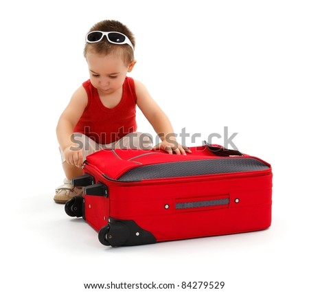 Little boy in sunglasses, preparing for vacation trip, opening or closing red suitcase - stock photo