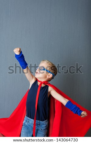Little boy in super hero costume pretending to fly against blue wall - stock photo