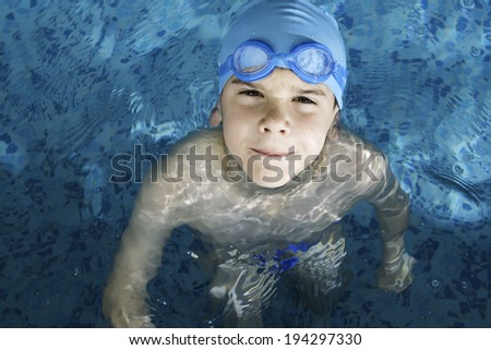 Little boy in swimming pool. Blue swimming pool.