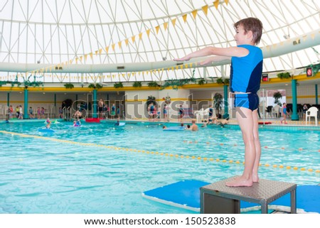 Little boy in swimming pool wearing blue life vest ready to take a dive - stock photo